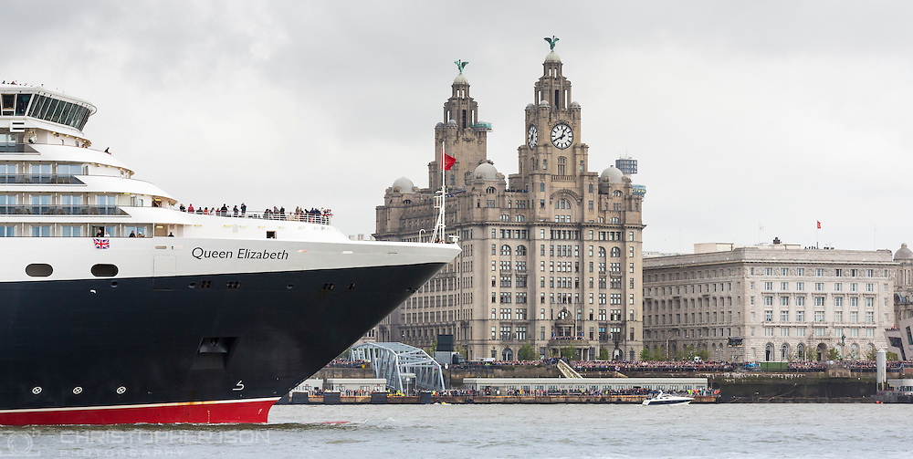 Cunard Lines' Queen Elizabeth passes the Royal Liver Building and the Cunard Building (right) as their fleet gather together in spectacular fashion in Liverpool, its spiritual home, as the company marked its 175th anniversary. The historic lines' three ships, the largest passenger ships ever to muster together on the River Mersey, lined up just 130 metres apart in the river.<br /> Picture date Monday 25th May, 2015.<br /> Picture by Christopher Ison. Contact +447544 044177 chris@christopherison.com