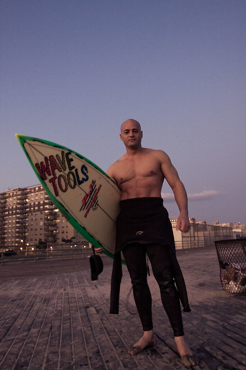 A surfer poses with his surfboard on the boardwalk at Rockaway Beach, Queens, NY.