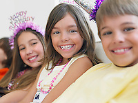 Children (7-12) sitting in row at birthday party selective focus