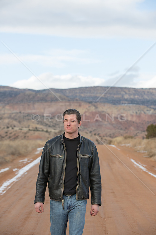 good looking man in a leather jacket outdoors on a dirt road in the mountains