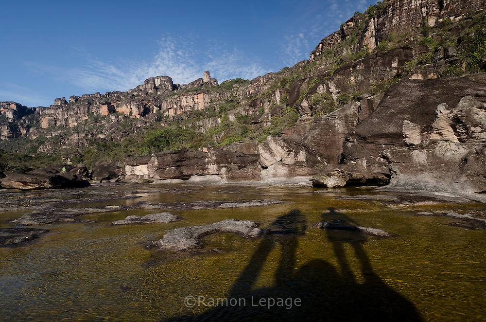 """AUYANTEPUY, VENEZUELA. Sombra de Excursionistas sobre el río Churum y vista de la Segunda Murralla.  El Auyantepuy es el mayor de los tepuis del Parque Nacional Canaima. En sus 700 kms2 alberga el salto angel o conocido por lengua indígena Pemon como """"Kerepacupai Vena; es la caída de agua más grande del mundo con sus 979 metros de altura. (Ramon lepage /Orinoquiaphoto/LatinContent/Getty Images)"""