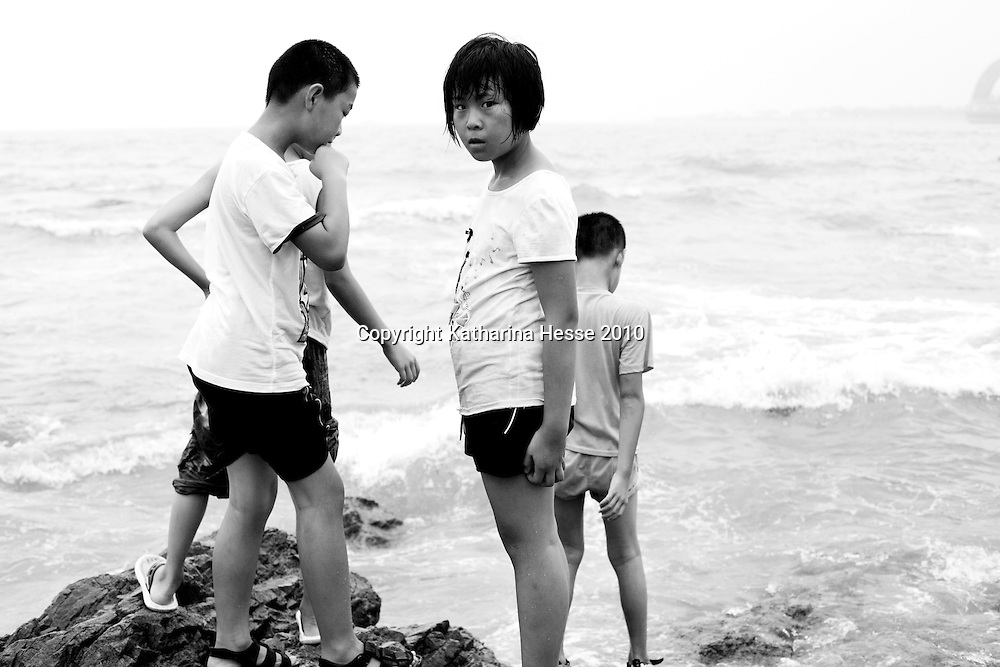 QINGDAO, AUG.22-2010 : a girl feels surprised by a photographer as she's playing with friends at the beach in Qingdao. Qingdao is one of China's  most renowned beach resorts  and  draws millions of visitors every year which is little by Chinese standards .