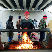 NEWS--   Homeless men try to keep warm around an abandoned barbeque grill turned into a wood-burning fireplace under the Buena Vista bridge in downtown San Antonio.  The men, including Sossiah (far right), all said they regularly stay in shelters.  The other men asked to not be identified.  ( Joshua Trujillo / Staff )