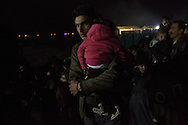 A Syrian father holds his daughter on the night of December 3, 2015 as a group of asylum seekers from Syria, Afghanistan and Iraq wait to cross the border into Macedonia. Hundreds of Syrians, Iraqis and Afghanis had been blocked from crossing the border for a day and a half by a group of asylum seekers predominantly from Iran, Morocco and Pakistan in protest of their inability to enter Macedonia due to recent border restrictions.