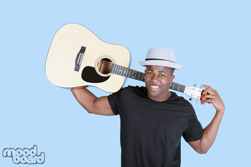Portrait of a young African American man carrying guitar over light blue background