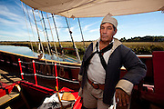 A costumed re-enactor portraits a colonial sailor on the working reproduction of the 17th century coastal trader the Adventure at historic Charles Towne Landing, the original settlement of Charleston, SC where English settlers established the city in 1670. The site is now a state park and historic site.