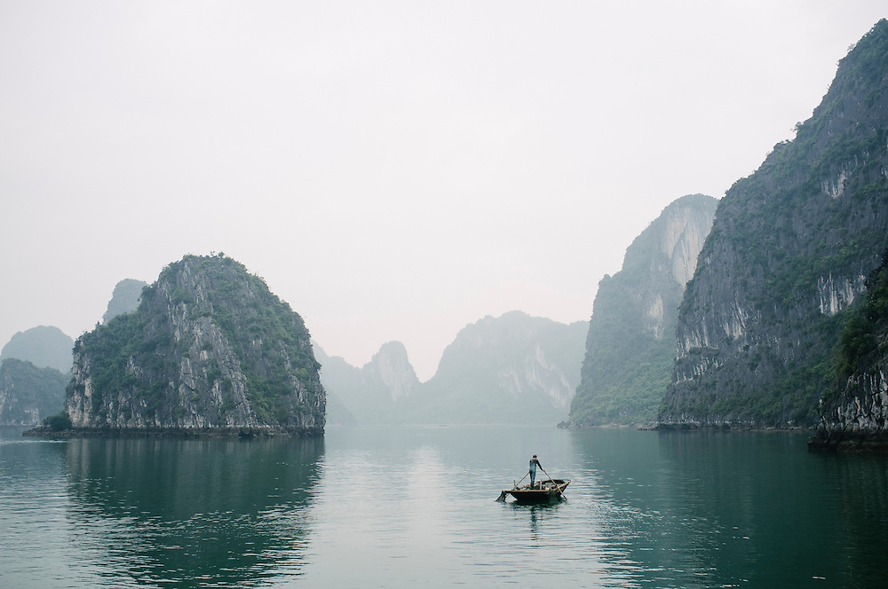 A fisherman rows his craft through Halong Bay, Vietnam