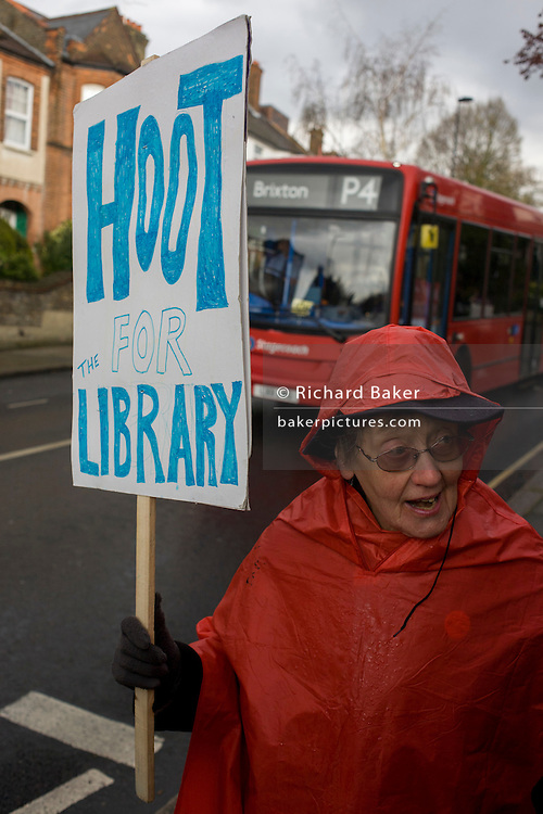 Wendy, in red, a lifelong campaigner and activist stands outside Carnegie Library in Herne Hill, south London asking passing motorists to hoot their support, while occupiers remain inside the premises on day 8 of its occupation, 7th April 2016. The angry local community in the south London borough have occupied their important resource for learning and social hub for the weekend. After a long campaign by locals, Lambeth have gone ahead and closed the library's doors for the last time because they say, cuts to their budget mean millions must be saved.