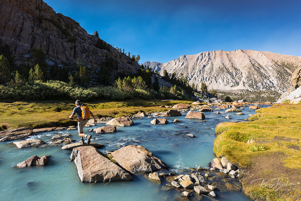 Hiker crossing stream in Sam Mack Meadow, John Muir Wilderness, Sierra Nevada Mountains, California