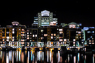 A Picture of St Katharine Docks at night, in London, England with building lights reflecting in the Marina waters