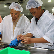 American Samoa Governor Lolo Moliga, is instructed by a master fish cleaner prior to the  innauguration ceremonies and festivities at the new Samoa Tuna Processor Cannery, (owned by TriMarine, Bellevue, Washington, USA), Satala, Tutuila, American Samoa. 1/24/15,  Photo by Barry Markowitz.