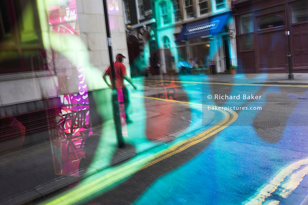 Seen through the abstract coloured mirrored glass of a backstreet bar, a passer-by walks to a street corner..