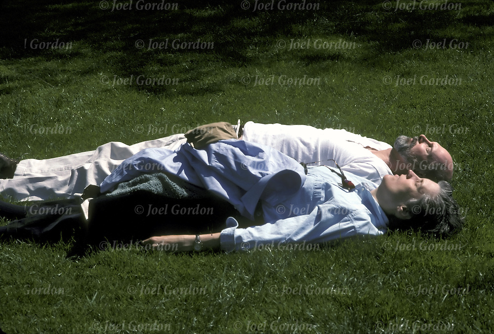 Affectionate senior couple, holding hands laying on grass in Central Park - NYC