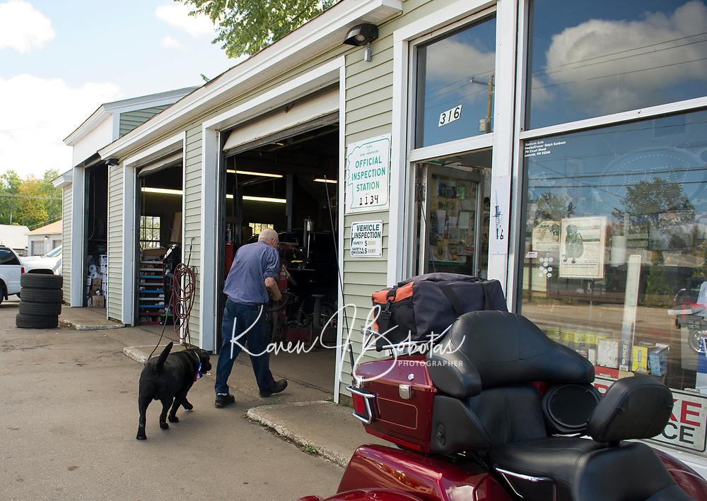 Lucky Jr follows Ralph Sanborn into the garage at Sanborn's Auto Repair.  (Karen Bobotas/for the Laconia Daily Sun)