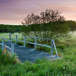 A footbridge spans a small stream in a field at Highland Farm in York, Maine.