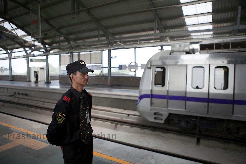 A guard looks on a s a metro train leaves the Kalkaji station of the Delhi Metro network in New Delhi, India, on Friday, October 22, 2010. Photographer: Prashanth Vishwanathan/HELSINGIN SANOMAT