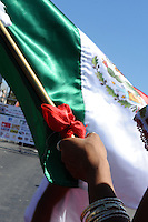 """A flag is held tight during the Mexican national anthem at Sunday's """"El Grito,"""" or """"The Cry of Independence"""" ceremony in Salinas."""