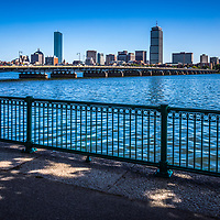 Boston skyline with Harvard Bridge and the Back Bay along the Charles River. Includes John Hancock Tower, Prudential Tower and a railing along the Dr. Paul Dudley White Bike Path. Boston Massachusetts is a major city in the Eastern United States of America.