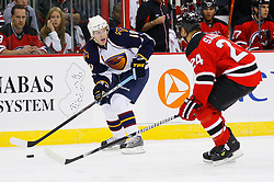 Nov 1, 2008; Newark, NJ, USA; Atlanta Thrashers center Bryan Little (10) skates with the puck against New Jersey Devils defenseman Bryce Salvador (24) during the first period at the Prudential Center.
