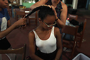 A girl has her hair fixed before her ballet class at the 'Ballet Santa Teresa' academy in Rio de Janeiro August 13, 2012. 'Ballet Santa Teresa', a non-governmental organization (NGO) gives children who live in areas with social risk, some suffering domestic violence, free ballet classes and other activities as a part of socio-cultural integration project. Photo by: Pilar Olivares