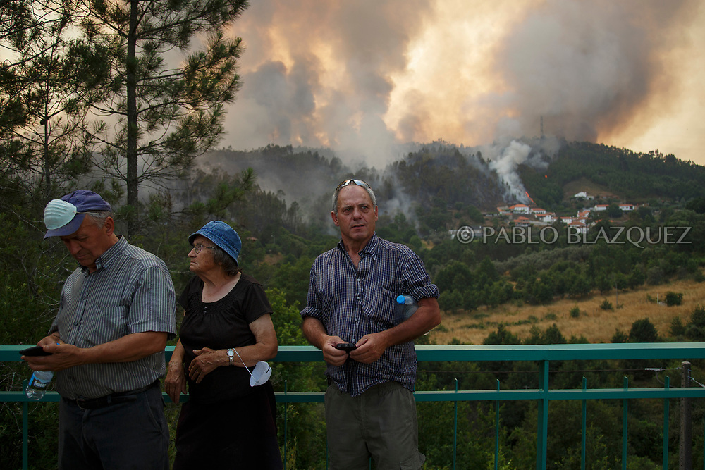 LEIRIA, PORTUGAL - JUNE 20:  Local people watch how flames approach to Mega Fundeira village after a wildfire took dozens of lives on June 20, 2017 near Picha, in Leiria district, Portugal. On Saturday night, a forest fire became uncontrollable in the Leiria district, killing at least 62 people and leaving many injured. Some of the victims died inside their cars as they tried to flee the area.  (Photo by Pablo Blazquez Dominguez/Getty Images)