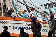 Sept. 27, 2009 -- PATTANI, THAILAND:  Crewmen on fishing boat and workers on the dock wait to start work as a fishing boat returns to port in Pattani, Thailand.  Fishing is the main industry in Pattani, one of just three Thai provinces with a Muslim majority. Thousands of people, mostly Buddhist Thais and Burmese Buddhist immigrants, are employed in the fishing industry, either crewing ships, working in processing plants or working in the ship building and refreshing yards.  Photo by Jack Kurtz / ZUMA Press