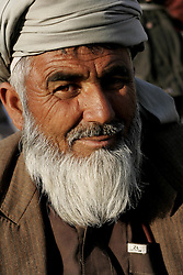 A bearded man sits in a market along the Kabul river in Kabul, Afghanistan.