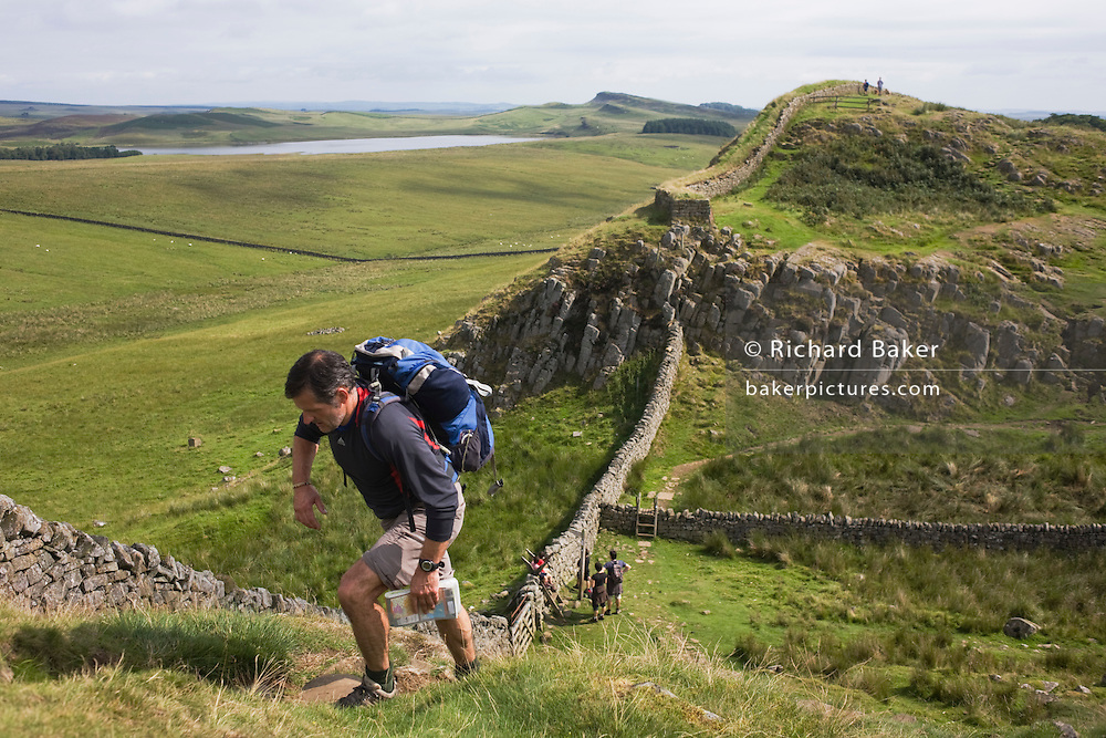 Walker climbs steep path on Roman Emperor Hadrian's Wall, once the northern frontier of Rome's empire from Barbarian tribes.