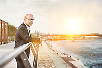 Portrait of thoughtful mature businessman leaning on railing