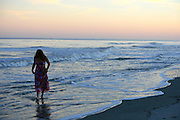 Red haired woman walking in morning surf, holding up long dress so it won't get wet. Sunrise sunset.