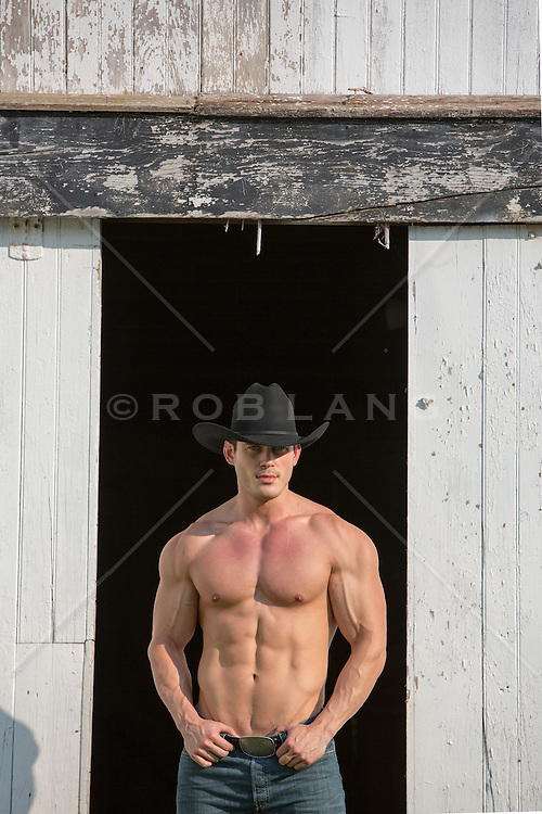 sexy masculine cowboy  without a shirt on a ranch