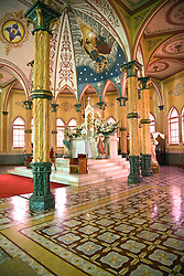 Zarcero, Alajuela, Central Highlands:  Altar and nave of the Iglesia de San Rafael, known as the pink and white church.  It was built in 1895 with an exterior of metal siding and a painted interior of faux bois and marble.  It is one of the most beautiful painted churches in the world.