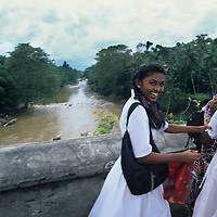 (MR) Sri Lanka, School girls walk home on bridge near town of Kandy