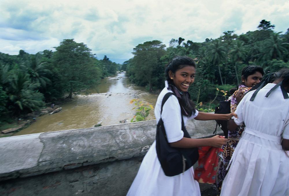(MR) Sri Lanka, School girls walk home on bridge near town of Kandy