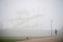 © Licensed to London News Pictures. 17/12/2016. London, UK. A jogger in Hyde Park passes  Winter Wonderland - almost hidden in the fog.  Parts of the UK are swathed in thick fog this morning. Photo credit: Ben Cawthra/LNP