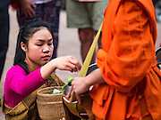 "12 MARCH 2016 - LUANG PRABANG, LAOS: A Lao woman gives alms to Buddhist monks during the morning tak bat in Luang Prabang. Luang Prabang was named a UNESCO World Heritage Site in 1995. The move saved the city's colonial architecture but the explosion of mass tourism has taken a toll on the city's soul. According to one recent study, a small plot of land that sold for $8,000 three years ago now goes for $120,000. Many longtime residents are selling their homes and moving to small developments around the city. The old homes are then converted to guesthouses, restaurants and spas. The city is famous for the morning ""tak bat,"" or monks' morning alms rounds. Every morning hundreds of Buddhist monks come out before dawn and walk in a silent procession through the city accepting alms from residents. Now, most of the people presenting alms to the monks are tourists, since so many Lao people have moved outside of the city center. About 50,000 people are thought to live in the Luang Prabang area, the city received more than 530,000 tourists in 2014.       PHOTO BY JACK KURTZ"