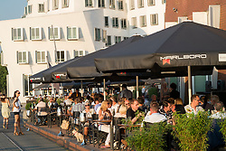 Busy restaurants at Neuer Zollhof buildings designed by Frank Gehry in Medianhafen in Dusseldorf Germany