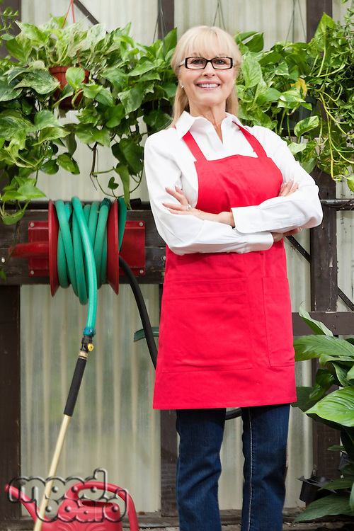 Portrait of a senior gardener with arms crossed in greenhouse