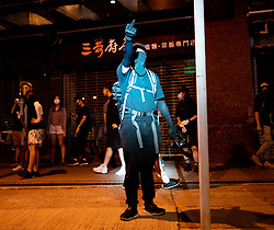 Hong Kong, China. 9th October 2019. Large peaceful crowd gathered to sing songs at MOStown mall in Ma On Shan in solidarity with several security guards who were arrested by police this week. Later small group of protestors went to nearby Shatin Divisional Police Station and shouted abuse at the police and threw objects. Riot police later charged but no arrests made. Protestor in police spotlight makes gesture to them. Iain Masterton/Alamy Live News.