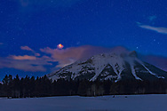 The total eclipse of the Moon over a peak of the Continental Divide at the Crowsnest Pass area of the Canadian Rocky Mountains in southwest Alberta, before dawn on the morning of January 31, 2018. The Moon was setting into the west. <br /> <br /> The Moon is just south (left) of the large binocular star cluster, M44, or the Beehive Cluster in Cancer.<br /> <br /> Shortly after this, clouds wafting off the peak engulfed the Moon and I lost sight of it. However, this was at 6:44 am MST, about 20 minutes before the end of totality. <br /> <br /> This was a much publicized Blue Moon and Supermoon eclipse. <br /> <br /> This is a blend of a 15-second exposure for the sky and foreground, and a shorter 1-second exposure for the Moon to prevent its disk from being overexposed, despite it being dim and deep red in totality. Both were at f/2.8 with the 50mm Sigma lens on the Canon 6D MkII at ISO 1600. Untracked, so the stars are trailed.