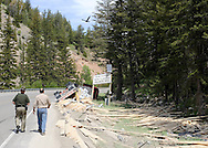 A semi-truck driver out of Rigby, Idaho explains the situation to the Wyoming Highway Patrol on Monday after flipping his rig and spilling a load of lumber while entering Hoback Canyon.