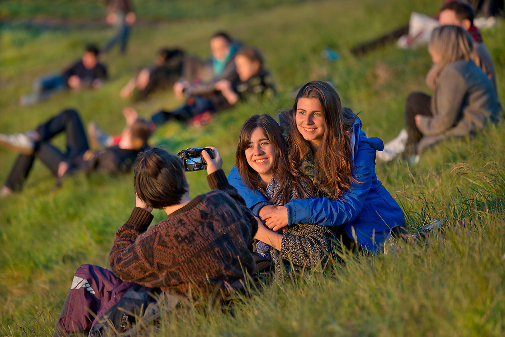 Young people gather on Calton Hill for sunset, Edinburgh, Scotland