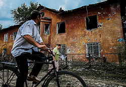 Local residents pass damaged house after Ukranian army shelling downtown of Khartsyzk (24km from Donetsk), Ukraine, 18 August 2014. Within a few weeks  the Ukrainian army continues shelling the living suburbs of Donetsk hundreds of homes destroyed more than half the city's population had fled their homes. At night the damaged power line supply pumping station feeding drinking water to the city of more than 500 thousand remaining residents do not have access to water.