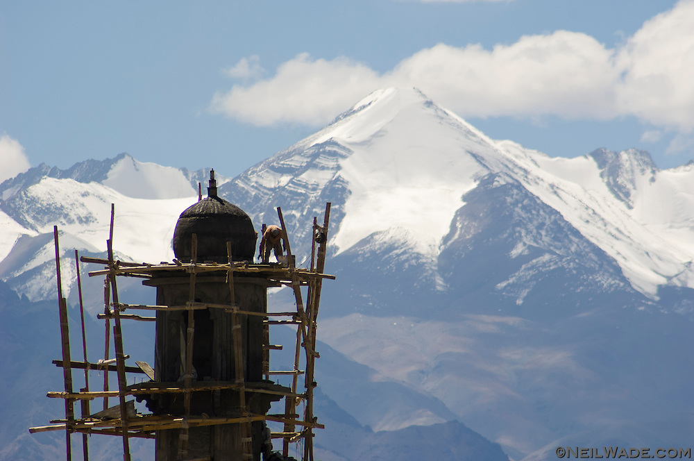 A worker works on a new minaret for one of the mosques in Leh, India as the formittable peak of Stok Kangri looms.