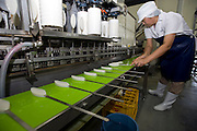 A staffer places freshly molded sasa-kamaboko onto a conveyor belt prior to baking at Oizen Shoten's factory in Tome City, Miyagi Prefecture, Japan on 11 Sept. 2012.  Photographer: Robert Gilhooly