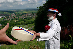 UK ENGLAND COOPERS HILL 31MAY04 - Master of Ceremonies Rob Seex hands over the worthy prize before contestants throw themselves off the top of a steep 200-metre slope in pursuit of a 7-pound Cloucester Cheese. The cheese rolling is one of the oldest customs to have survived some saying, for hundreds of years, even pre-Roman times. The ceremony is reported to.have taken place originally at midsummer and to have been moved to Whitsun in early Saxon times. Some say it is a relic of an old heathen festival to celebrate the return of spring and.others say, when held in midsummer, it represented the waning of the sun as summer reached its height, but no one knows for sure....jre/Photo by Jiri Rezac..© Jiri Rezac 2004..Contact: +44 (0) 7050 110 417.Mobile:  +44 (0) 7801 337 683.Office:  +44 (0) 20 8968 9635..Email:   jiri@jirirezac.com.Web:     www.jirirezac.com