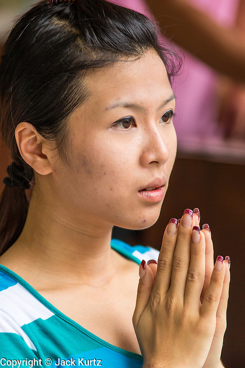 27 SEPTEMBER 2012 - BANGKOK, THAILAND:  A woman prays at the Erawan Shrine in Bangkok. The Erawan Shrine is a Hindu shrine in Bangkok, Thailand, that houses a statue of Phra Phrom, the Thai representation of the Hindu creation god Brahma. A popular tourist attraction, it often features performances by resident Thai dance troupes, who are hired by worshippers in return for seeing their prayers at the shrine answered. The Erawan Shrine was built in 1956 as part of the government-owned Erawan Hotel to eliminate the bad karma believed caused by laying the foundations on the wrong date. The hotel's construction was delayed by a series of mishaps, including cost overruns, injuries to laborers, and the loss of a shipload of Italian marble intended for the building. Furthermore, the Ratchaprasong Intersection had once been used to put criminals on public display. An astrologer advised building the shrine to counter the negative influences. The Brahma statue was designed and built by the Department of Fine Arts and enshrined on 9 November 1956. The hotel's construction thereafter proceeded without further incident. In 1987, the hotel was demolished and the site used for the Grand Hyatt Erawan Hotel.      PHOTO BY JACK KURTZ