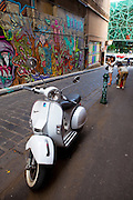 Asian tourists looking at Graffiti and parked moped on Hosier Lane, Melbourne. Federation Square Atrium in the background