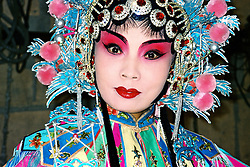 China, Taiyuan, 2008. A female Chinese opera performer waits in the wings for her entrance. Traditional costumes can often be quite heavy, and makeup elaborate.