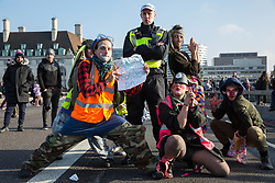 London, UK. 17th November, 2018. A troupe of clowns supports environmental campaigners from Extinction Rebellion blocking Westminster Bridge, one of five bridges blocked in central London, as part of a Rebellion Day event to highlight 'criminal inaction in the face of climate change catastrophe and ecological collapse' by the UK Government as part of a programme of civil disobedience during which scores of campaigners have been arrested.